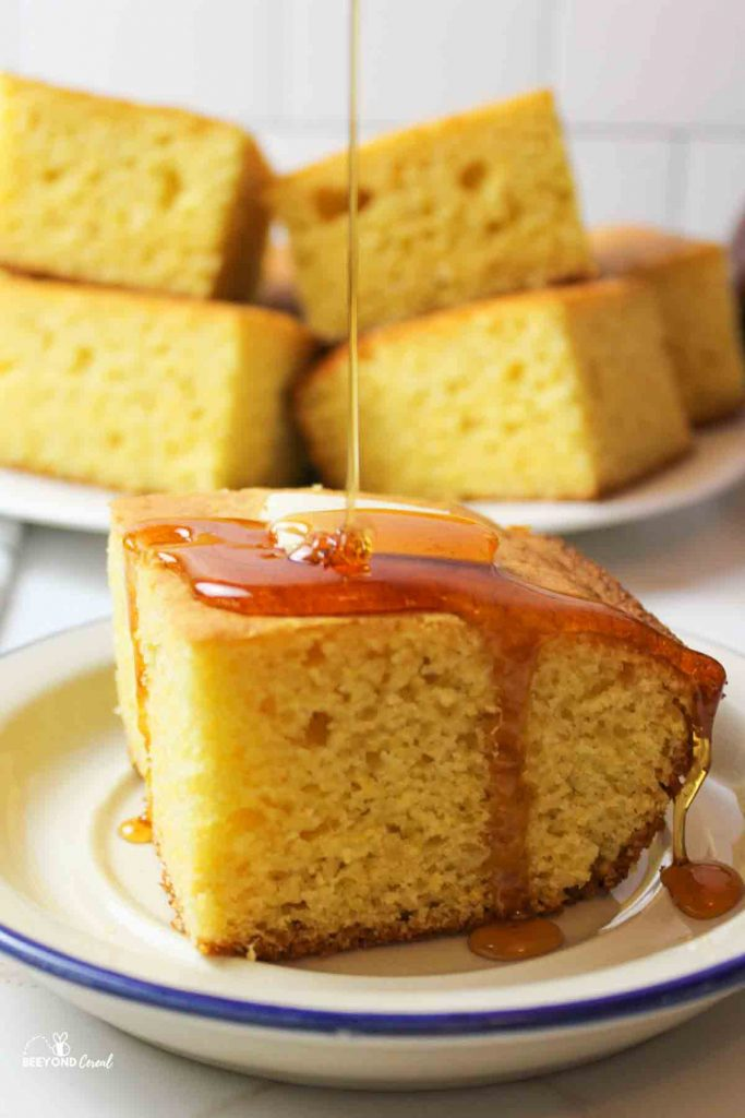 honey being drizzled on top of a butter topped slice of cornbread on a plate