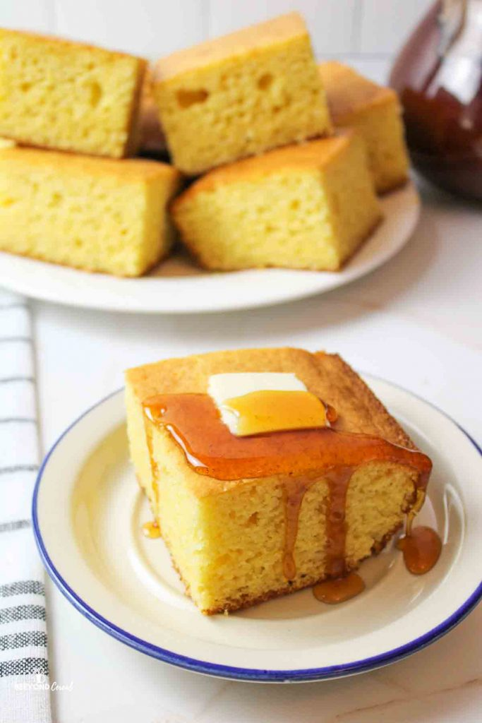 a slice of cornbread on a blue rimmed plate topped with a pad of butter and honey
