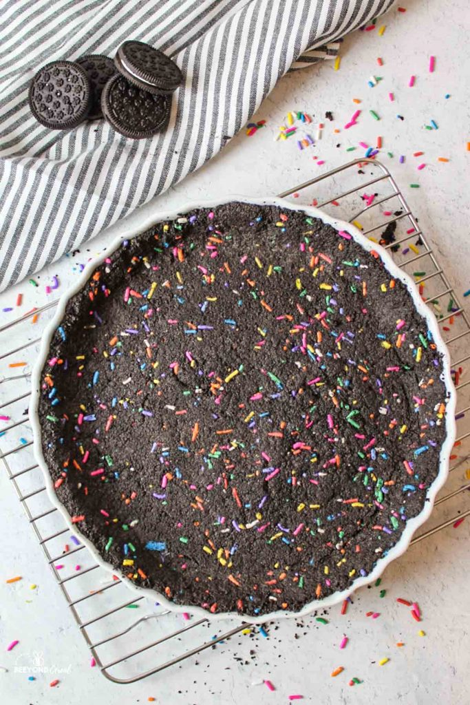 an oreo sprinkle crust in a baking dish on a wire rack with scattered sprinkles around it and oreo cookies off to the side
