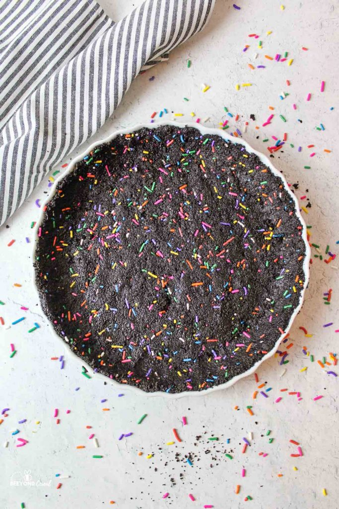 aerial shot of an oreo sprinkle crust pressed into a tart pan