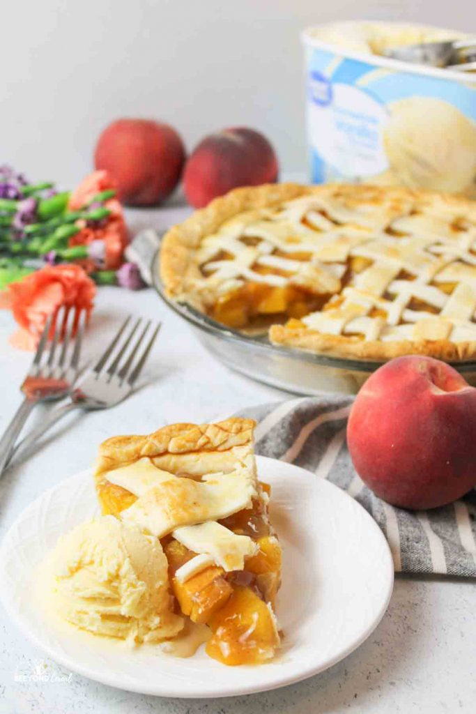 a sliced peach pie with ice cream in front and more pie and fresh peaches in background