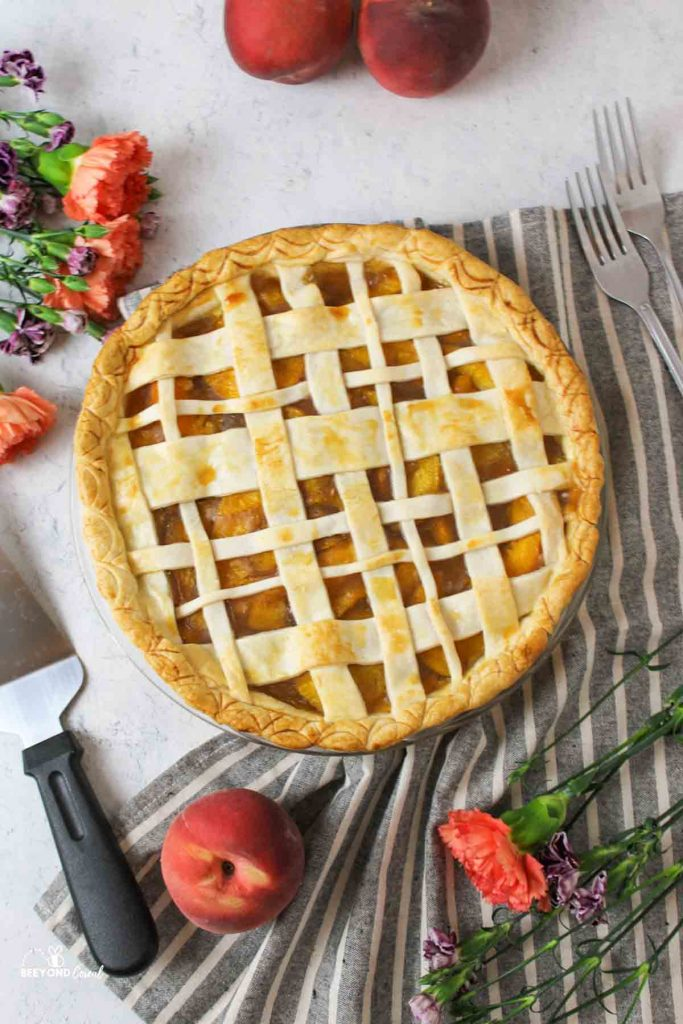 peach pie with lattice top surrounded by fresh peaches and flowers