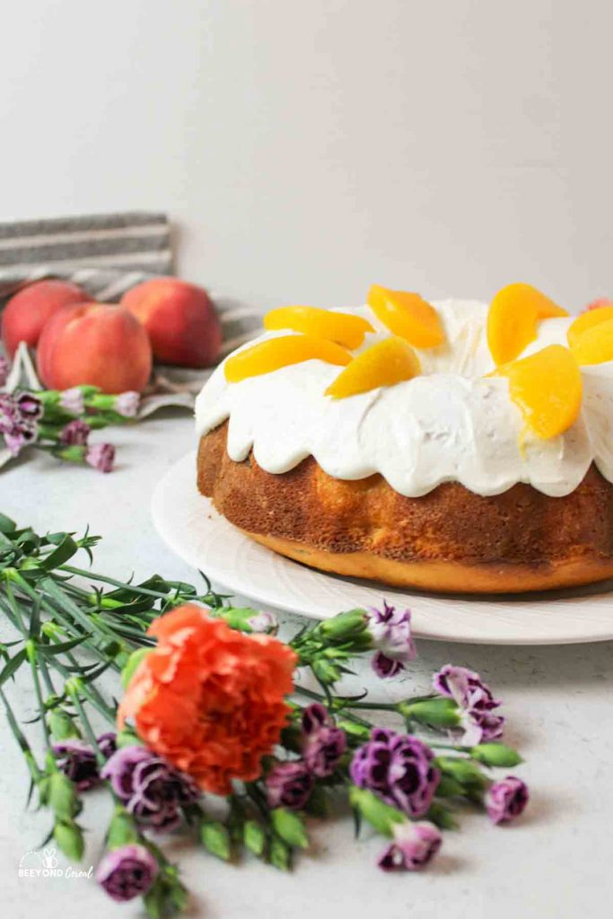 a side view of a peaches and cream bundt cake with fresh flowers and peaches to the side