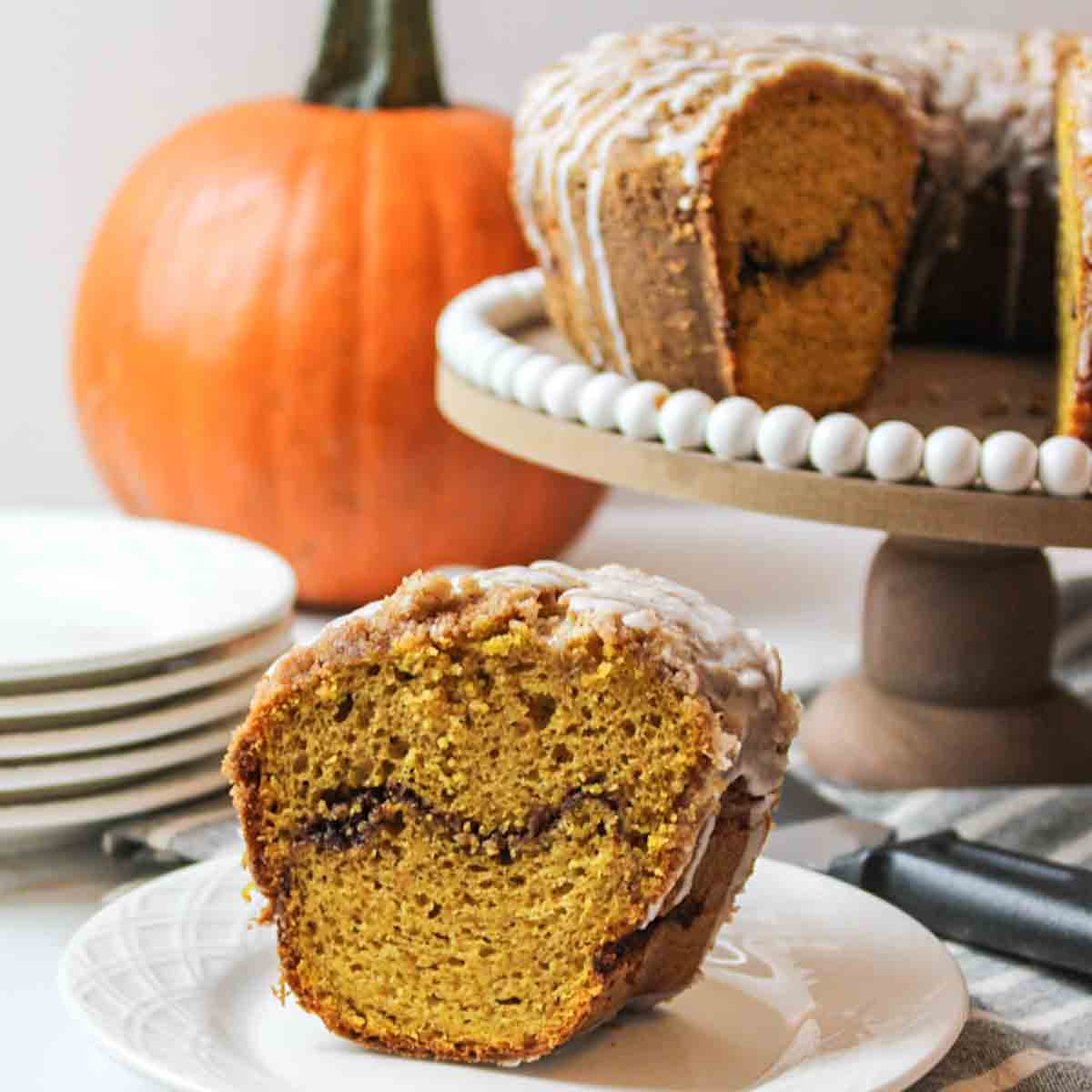 a slice of pumpkin coffee cake up close with more cake and a pumpkin in the background