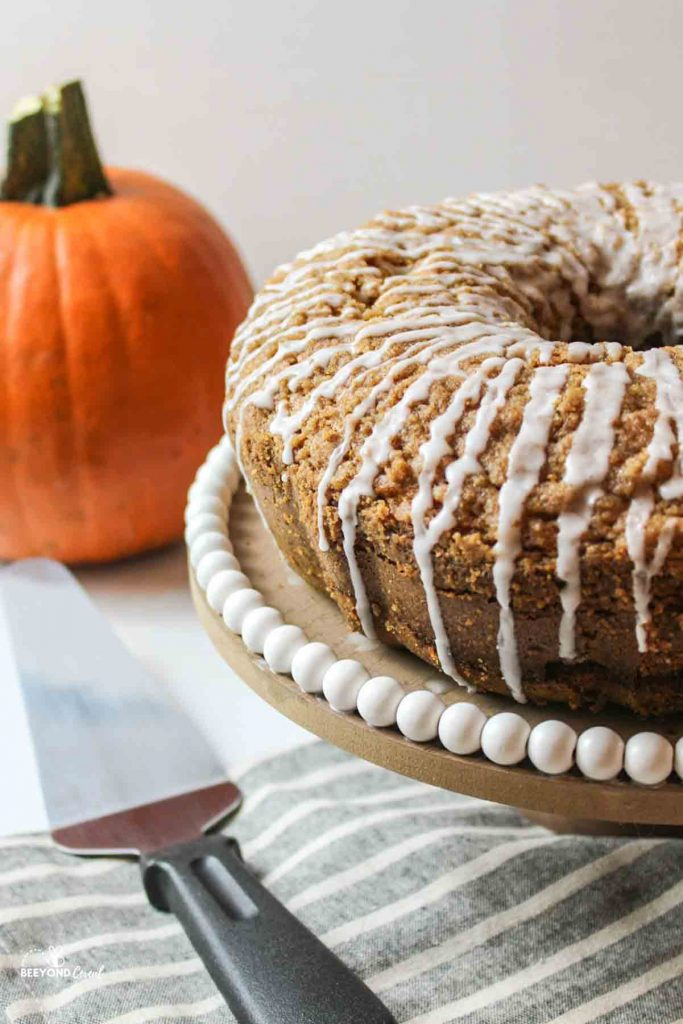 glaze topped pumpkin coffee cake on a cake stand with a server to the side and pumpkin in the background
