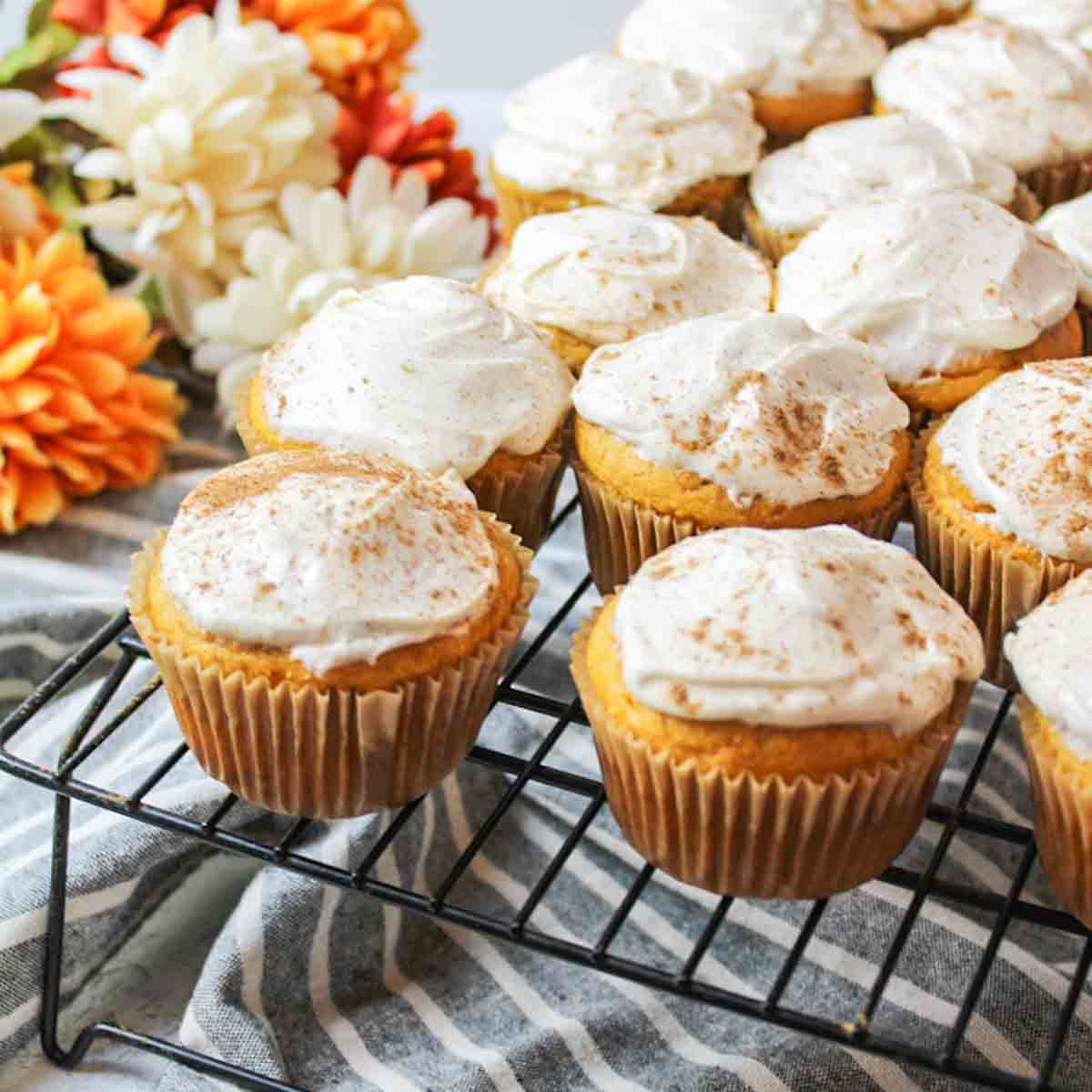 a close up of frosted pumpkin cupcakes ona wire rack