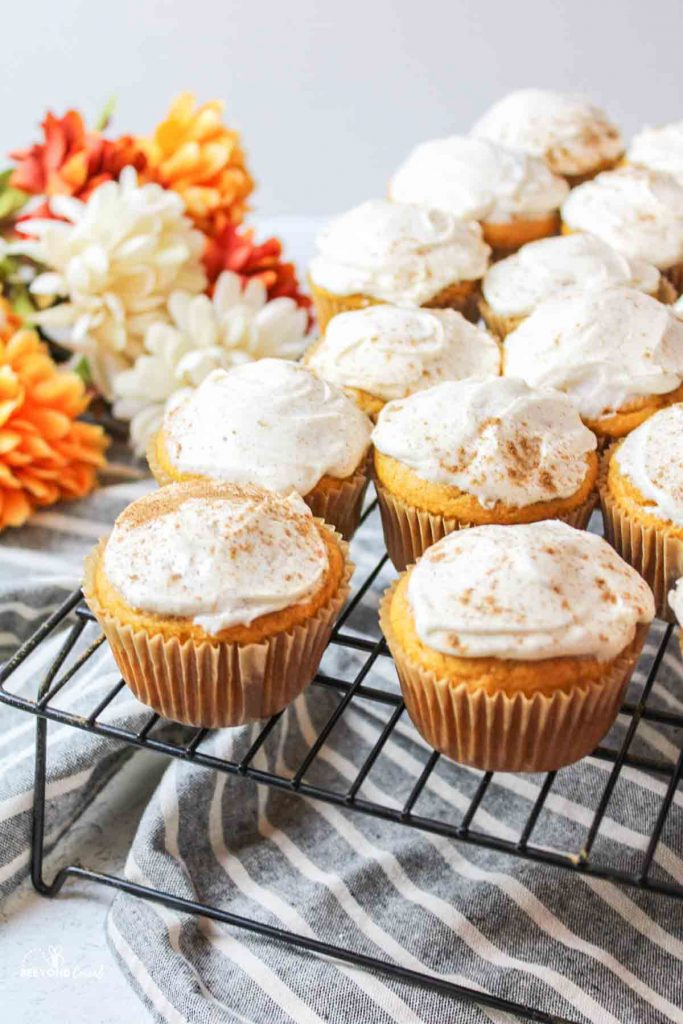 frosted pumpkin cupcakes on a wire cooling rack with flowers in background