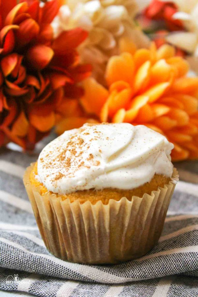 a spiced pumpkin cupcake with cream cheese frosting