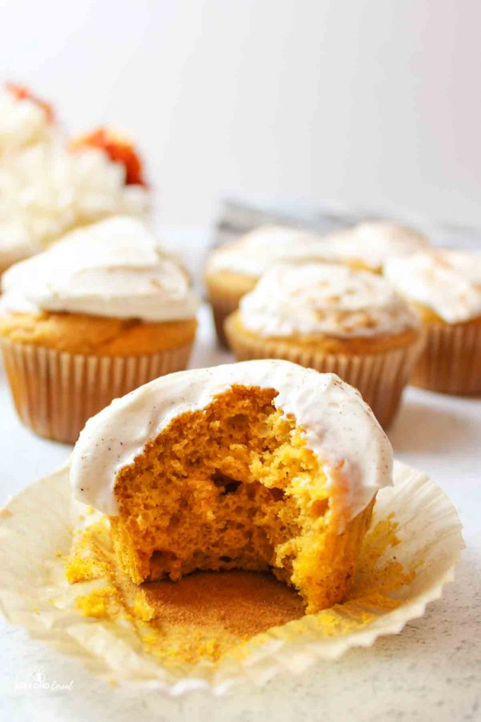 a cream cheese frosted pumpkin cupcake with a bite taken out of it