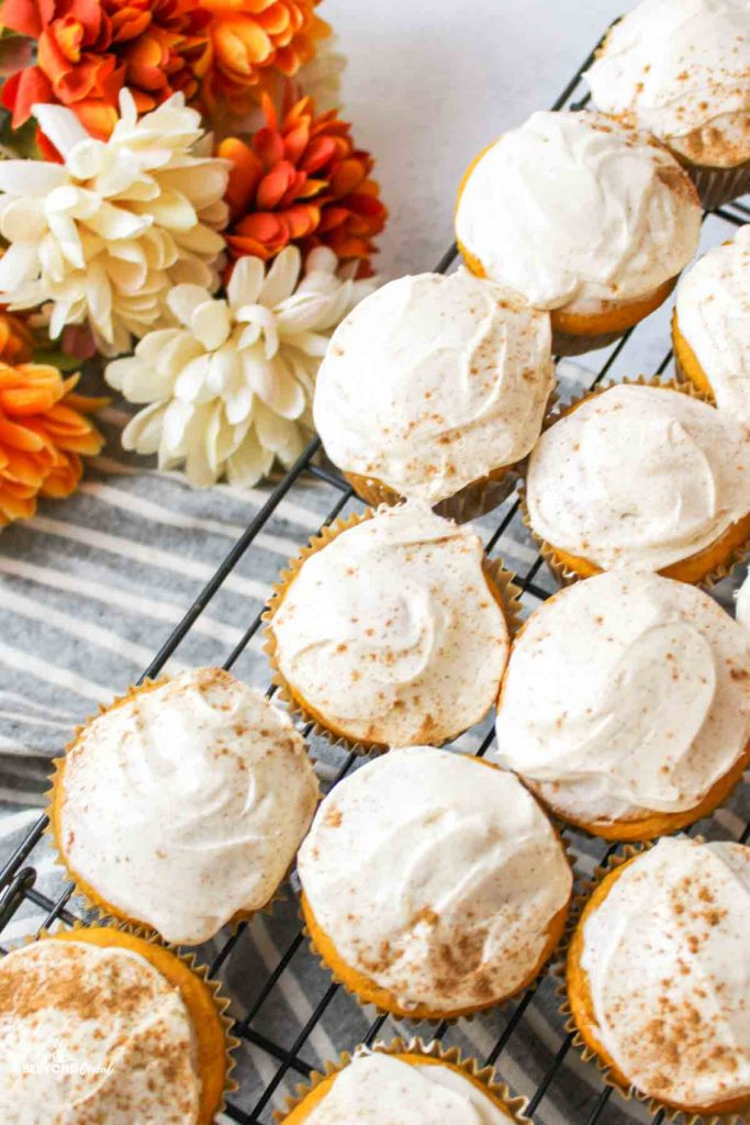 aerial view of several forsted and spiced cream cheese topped pumpkin cupcakes on a wire rack