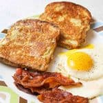 an upclose plate of a french toast breakfast on a plate with eggs, bacon, and two slices of french toast