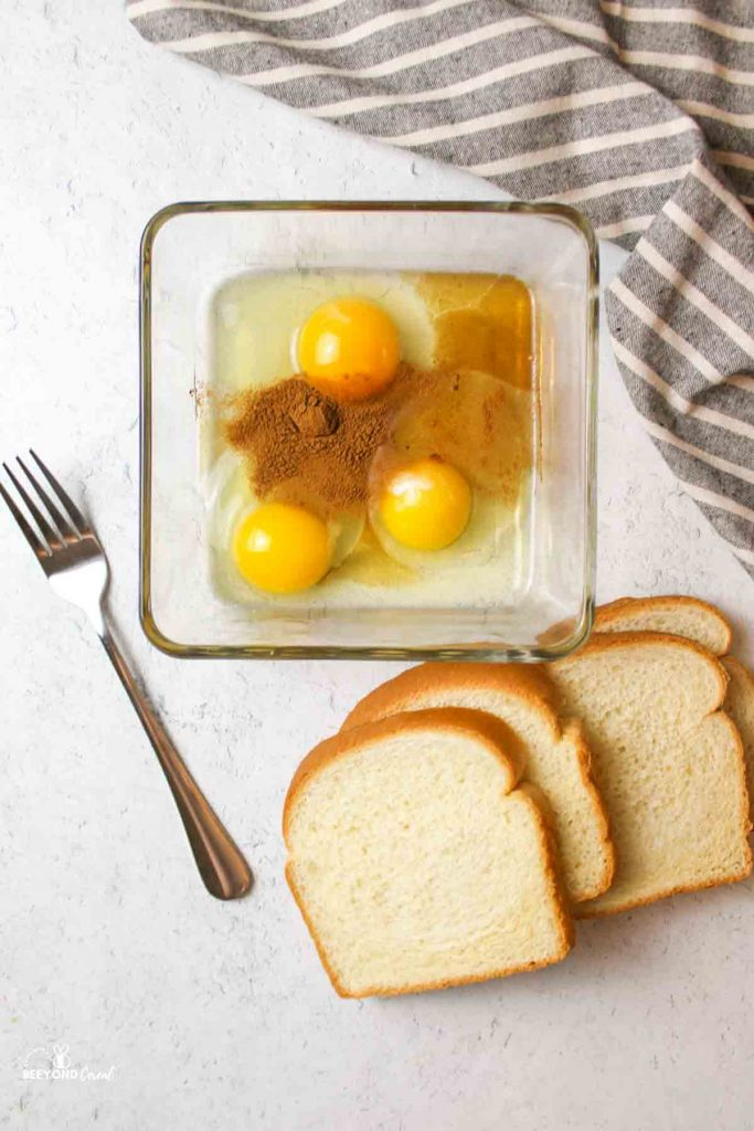 bread slices next to a glass container of eggs, vanilla, and cinnamon and a fork to the side