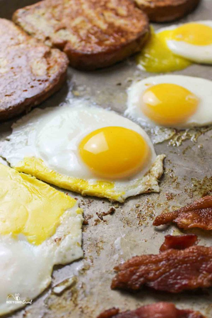 upclose view of a cooked egg on a sheet pan with bacon in front and french toast in the background