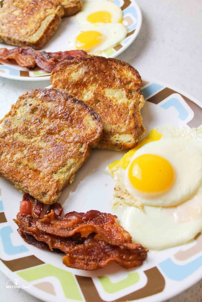 eggs, bacon, and french toast on plates