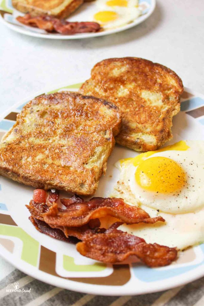 two slices of french toast next to cooked crispy bacon and sunny side up eggs on a plate