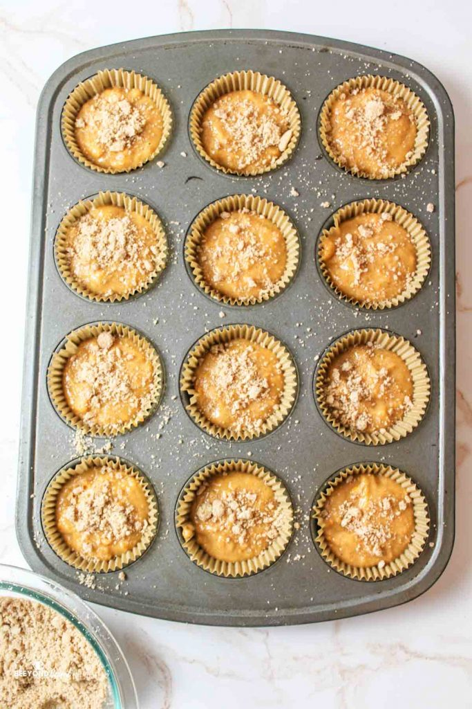 sweet potato muffin batter in a muffin tray with streusel on top