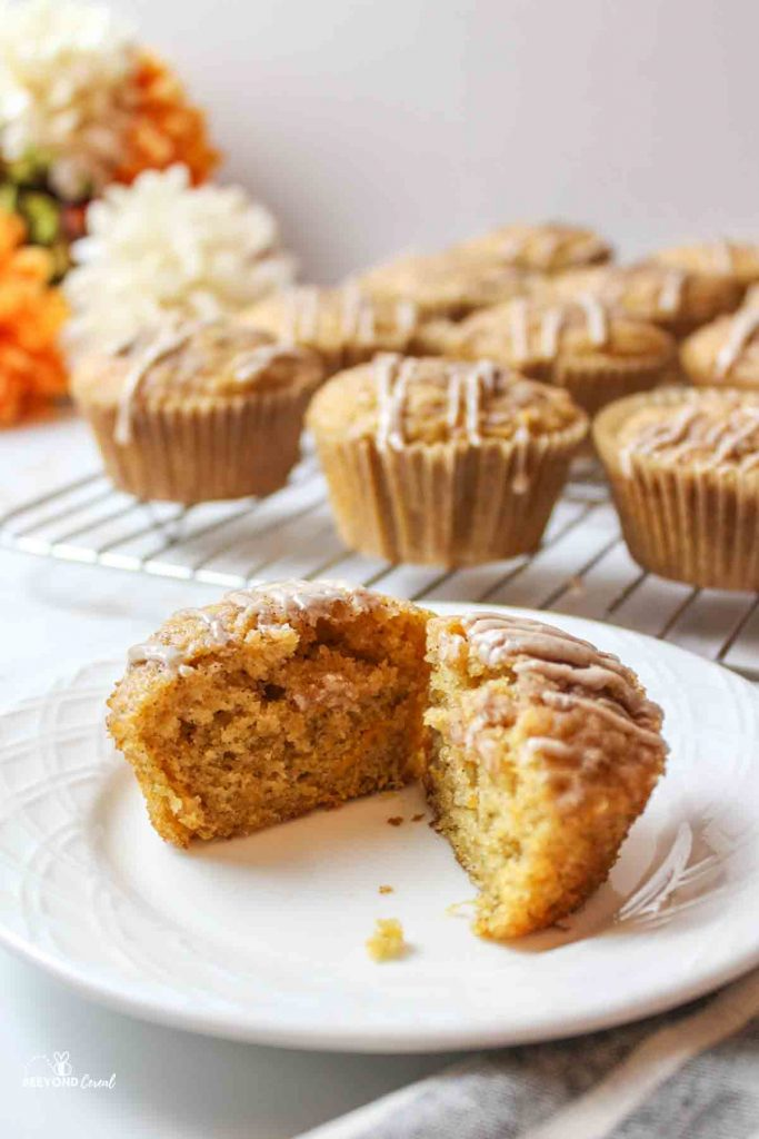 a sliced sweet potato muffin on a plate with more on a rack in the background