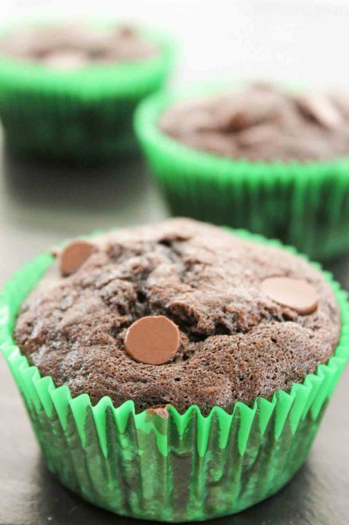 an upclose view of a chocolate zucchini muffin with chocoalte chips in a green muffin liner