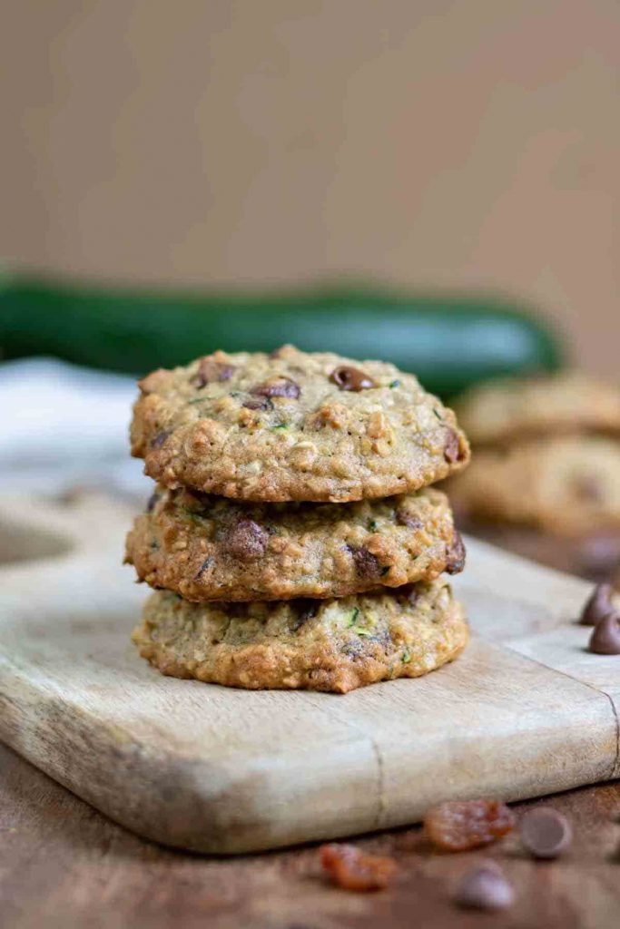 three stacked zucchini cookies on a wooden cutting board