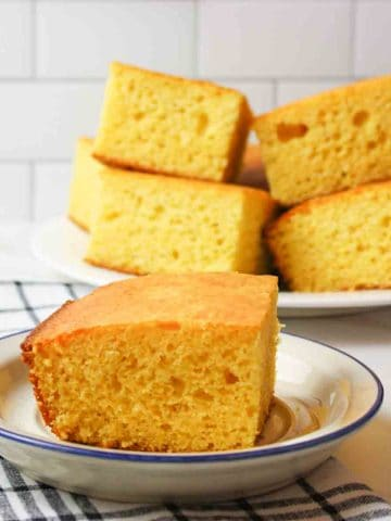 a slice of cornbread on a blue rimmed plate with more stacked pieces of cornbread in the background