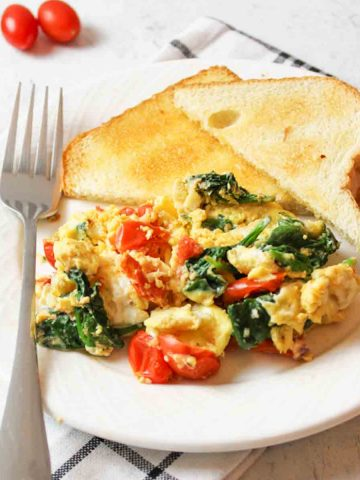 aplate filled with Scrambled Eggs with Spinach and Tomatoes and two sliced pieces of toast with a fork resting on the plate