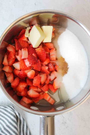 a corner of the round fresh strawberry pie wth whipped cream